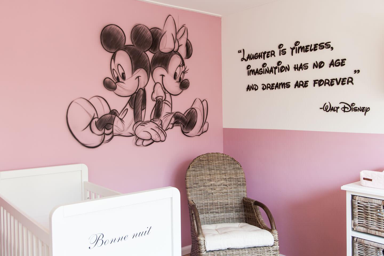 Muurschildering Mickey met quote van Walt Disney in babykamer.